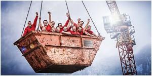 Business - Fotografie Gruppenbild einer Handwerkstruppe (Dachdecker) in einem Container, der vom Kran in der Luft gehalten wird.
